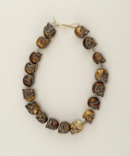 String of 18 beads carved in the shape of human skulls.