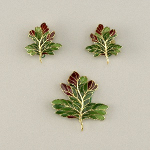 Two earclips and a brooch, each in the form of an oak leaf with a gold stem and veining, filled with deep green and dark red plique-à-jour enamel.  Earclips have plastic ear cushions.  Attached to each piece by a green cord is a circular stamped lead seal with mark.