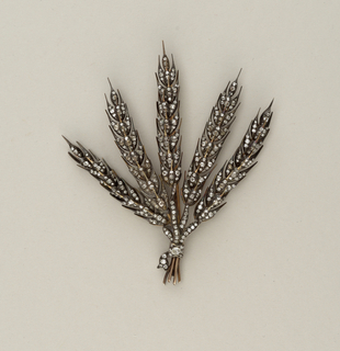 Brooch consisting of large spray of leaves done in 18 karat gold and paved in diamonds.  The stalks of what in this brooch are set on thin wires that vibrate easily with the wearer's movements.