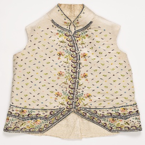 Gentleman's waistcoat with floral design concentrated at front opening and at pocket area, with small sprigs forming an open lattice in the ground. Small standing collar.