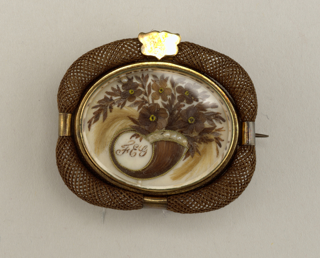 "Framed gold oval showing horn-of-plenty made of hair, seed pearls and pailettes and the initials ""FEG"".  Surrounded by tightly woven brown human hair."