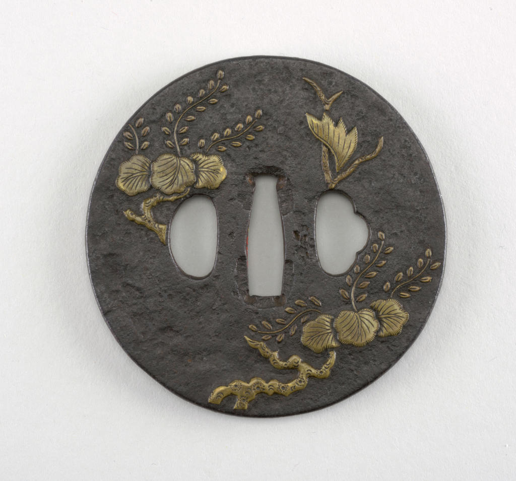 Tsuba are disk-shaped metal sword guards that prevent the palm of the hand from slipping past the hilt and onto the blade. This tsuba was made during the Keichō period (1596–1615), a time when metalsmiths were beginning to transition from the production of Kyoto swords (old swords in traditional vernacular styles), and began to produce Shinto swords (new swords).   This iron tsuba is shinmaru gata (a true circle) in shape, has a migaki (smooth) surface, and is decorated with an inlaid brass design of a kakiwaki kiri (branch of the paulownia tree) with parted foliage.  The inlay technique known as tetsu was a specialty of the Heianjo school of brass inlay in a region of which Kyoto is the center. The suemon taka zogon inlay is high relief with thin, linear carving lines resembling hair.  At the center is the nakago-ana, an opening through which the sword passes. On either side are ryo-hitsu, openings for the kozuka (utility knife) and the kogai (skewer tool). At left is sashi ura, the side which faces the blade, whose opening takes the hangetsu-kei (half moon) shape. Opposite is the more elaborately decorated sashi omote side, which faces the sword hilt. Its tri-lobed opening is of the suhama type, and symbolically represents the coastline of Horai, the holy island of the Immortals. Surrounding these openings, is the seppadai, a flat oval area that is migaki (burnished). The rim of the tsuba is angular, or kaku-mimi.