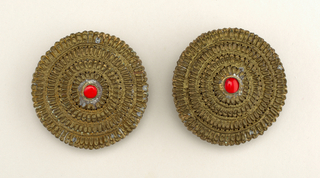 Pair of brass ear-plugs, round. Red Setting of glass on composition. Ornament, concentric circles (4) of grain-like pattern with holes punched to emphasize separate grains.