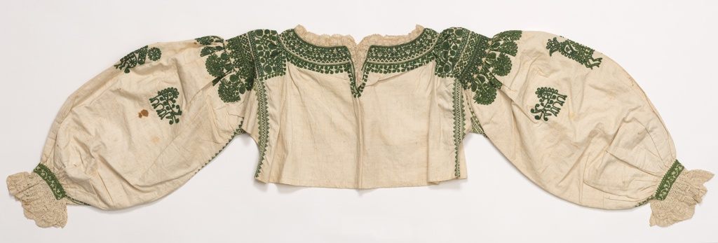 Woman's blouse densely embroidered in dark green on natural cotton. Long, full sleeves trimmed with bobbin lace at the cuff. Neck and shoulders embroidered with geometric and floral forms. Paschal lamb is on each sleeve.