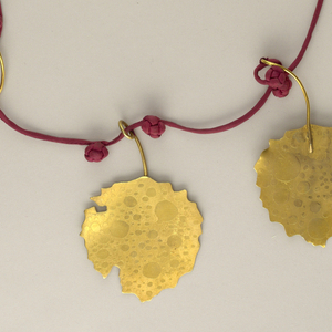 "Silk cord necklace with spaced decorative knots; nine flat brass ""leaves"" attached to metal hooks hang from cord."