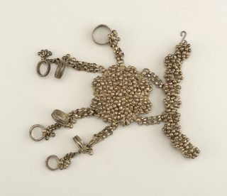 Hand or foot piece, silver, with small balls, in clusters, and seven pendant rings on chains.