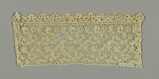 Binche style fragment with a scolling ribbon like design with snowballs and graided connections.  Narrow scalloped border made sparately and sewn on.