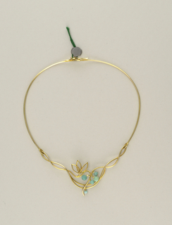 Wire-like appearance, stiff neckpiece with hooks for clasp; twisted vine-like metal with floral motif composed of five beads.