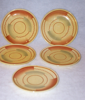 Circular plate with raised bottom rim.  Yellow background with straight and wavy brown lines forming concentric circles broken up by swatches of airbrushed brown and blue.
