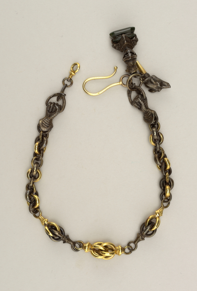 Watch chain of ornamental links of gold and steel; at either end, a mailed fist holding ring with snakes head. Two ornaments; bust in armor on pedestal. Watch key with wolf's head on top.