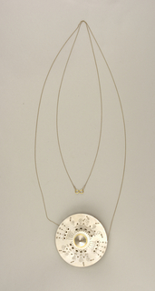 Disc pendant hanging from chain. The disc is decorated with allover pattern of cutouts, including spirals, asterisks, and lines. At its center, the disc incorporates a container for aromatic materials.