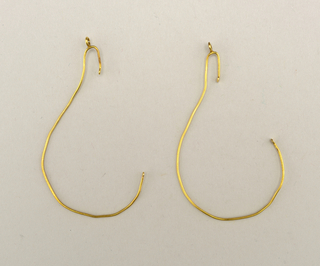 A) and B) Gold wire shaped to fit around ear; hook at bottom to hold earring.