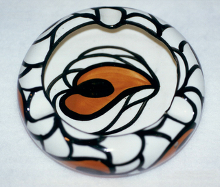 Circular form with grooved rim, outlined in black, that curves into the center.  Cream ground color patterned on interior and exterior with curving black lines and stylized orange leaves outlined in black with black centers.