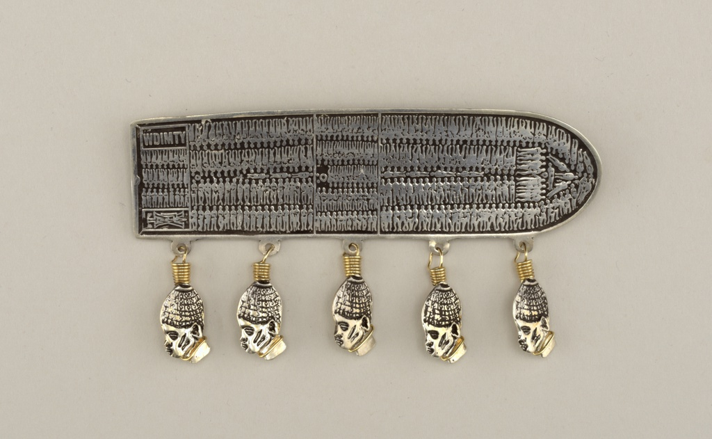 Modeled after diagram of a slave trade ship seen from above, showing the lower deck densely packed with a cargo of slaves; five heads of African slaves in profile hang from the lower edge.