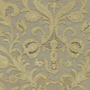 Long narrow scarf of ecru lace in a vertical, symmetrical design of scrolling serpentine branches and flowers springing from central ornamental motifs. Scalloped edge.
