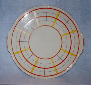 Circular flat plate on raised bottom rim with molded undulating edge and two bracing tab handles with an orange line.  Cream background with three concentric circular bands of orange forming a large central solid cream circle.  Orange alternates with thin black circles.  Surface divided into sixteen areas by alternating black and yellow radiating lines.