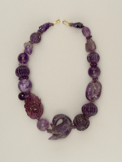 Necklace composed of large carved amethyst beads, opal details, carved swan and other textured beads.