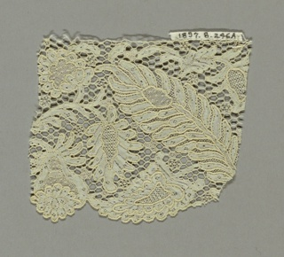 "Fragment of Argentan-style lace showing floral designs with large ornamental leaves and blossoms on a ground of ""brides bouclées."""