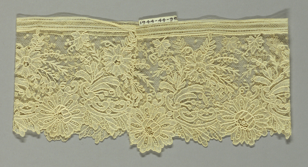Design of roses, leaves and scrolls. Lace borders joined to form cuffs.