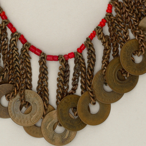 String of red beads, with metal chains and East Africa one cent coins suspended at regular intervals through holes in their centers.