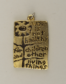 """Upright rectangular pendant with engraved decoration consisting of the slogan, """"war is not healthy / for children and other / living things,"""" interspersed between the leaves and stem of a stylized petaled flower. Small ring at top of pendant."""