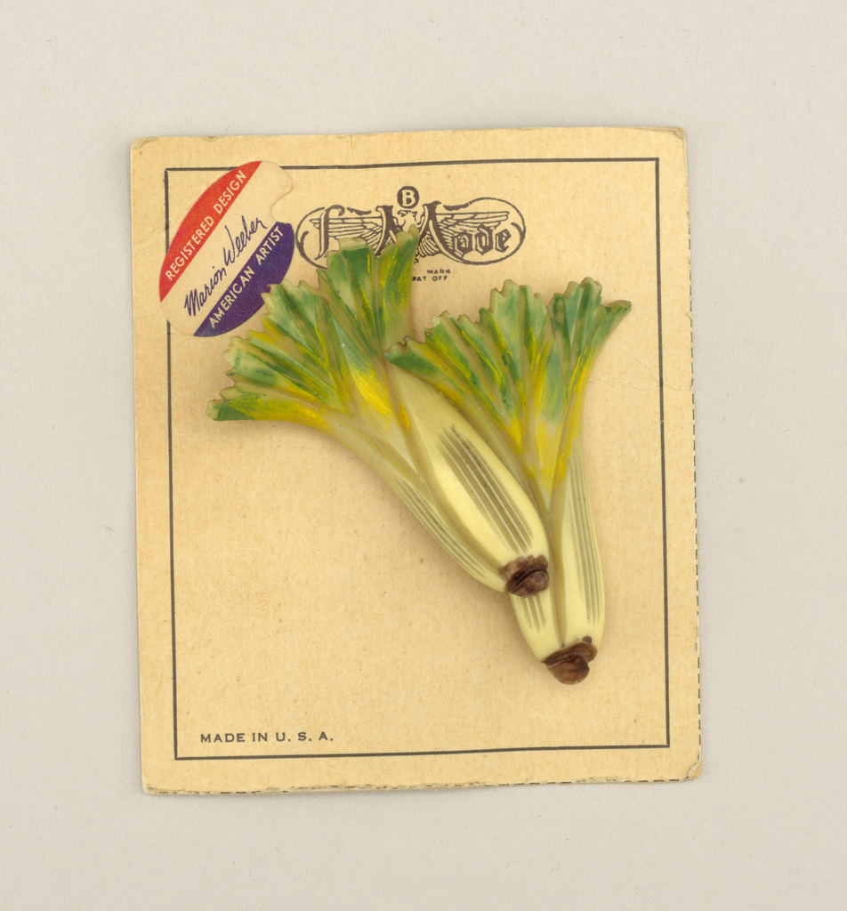 Brooch in the form two leafy bunches of celery, the green-yellow leaves tapering to off-white stalks with brown nubs; pinned to original display card.