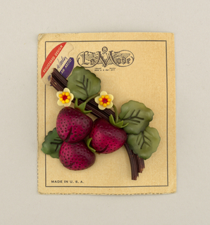 Brooch in the form of three red strawberries and two yellow blossoms surrounded by green leaves, all on a brown woody stem; pinned to original display card.