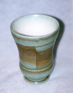 Cylindrical body curving at bottom to a circular base and then widening at the top lip.  One molded groove about two-thirds down the surface of the body.  Turquoise background creates a stripe effect with thick and thin horizontal airbrushed bands of brown and rust running down the vase.