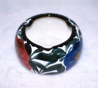 Circular squat body with an indented top rim, outlined in black, curving into the center.  White background patterned with stylized green leaves and poppies in orange, blue, and deep rose all with brown centers with dark brown dots.