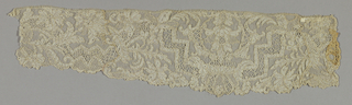 Fragment, probably a sleeve ruffle, has elaborate blossoms, leaves, stepped geometric shapes, and zigzags.