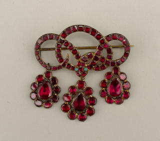 Ribbon-like brooch with three interwoven loops and three circular pendants hanging pendants with central oval garnet and small round garnets around each oval. Two small turquoise stones in above center pendant.