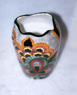 Vertical cylinder widening from bottom to an asymmetrical undulating top edge glazed with black.  Handpainted gray ground patterned with large stylized floral blooms in orange, burgundy, black, yellow, green, and blue.