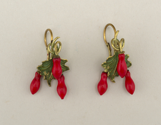 "Green-enameled fuchsia leaf with three red ""buds"", two of which depend from short chains at the back of the leaf.  Hinged earpiece."