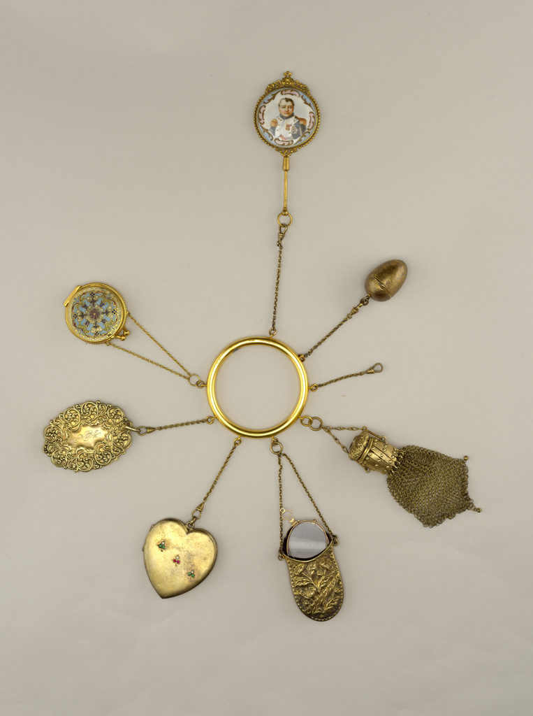 Seven components of various materials attached to simple, gold-washed hoop bracelet: a: Ring; b: Mirror; c: Egg;  d: Mesh bag; e: Eyeglass case; f: Eye glass; g: Heart shaped Locket; h: Memo pad; i: Compact; j: Pin cushion; k: string.