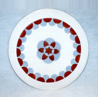 Flat and round form featuring central, flower-like motif of six overlapping lavender circles and one central lavender circle, over the center of which is superimposed a burgundy six-point star; six burgundy petal-like forms radiate outward from star; near permimeter and encircling central motif is a ring of burgundy semi-circles which overlap another ring of lavender semi-circles; all polychrome glazed decoration on an off-white ground.