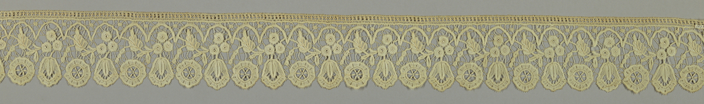 Duchesse-style pattern of leaf and flower sprays under arches with border showing alternating leaf and flower pattern.