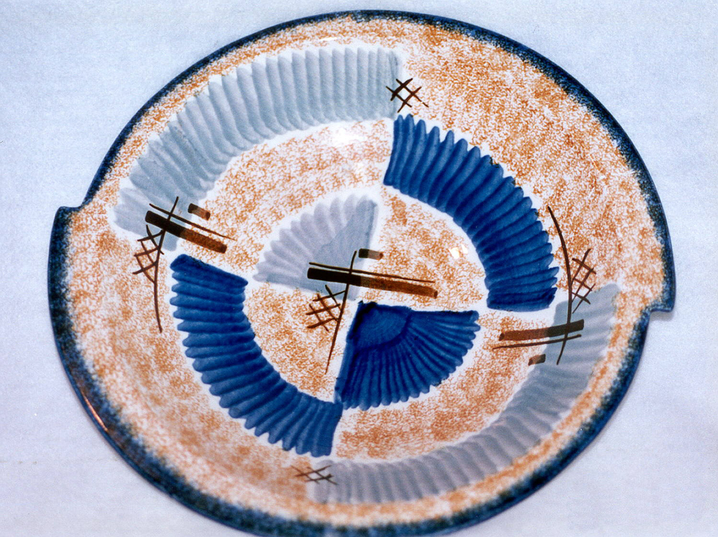 """Asymmetrical bowl appearing as if two semi-circles were joined together about one inch off sides, with raised bottom rim and flat top edge.  White background speckled with orange.  Edge lined in deep blue.  Abstract pattern consists of """"lined"""" patches of blue and gray.  Four areas of brown crossed lines.  Centered opposite quarter circles, one of blue and one of gray."""