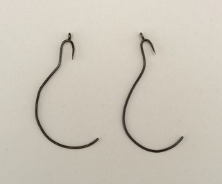 A) and B). Silver wire shaped to fit around ear; hook at bottom to hold earring.
