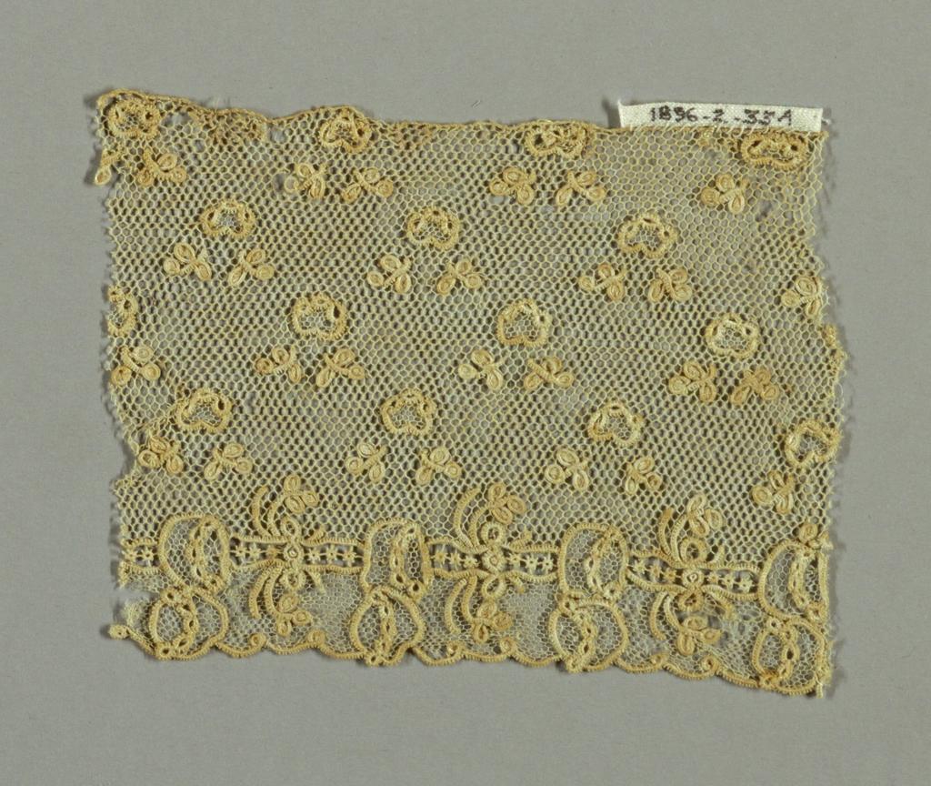 Alençon-style fragment with minute powdered floral design. Ground of brides tortillées.