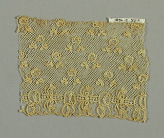 Alençon-style fragment with minute powdered floral design. Ground of brides tortillées.