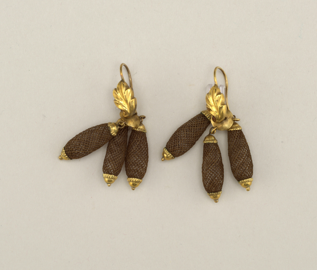 Pair of earrings in design of three pendants of brown hair arranged around a disc placed below one gold leaf on a gold ring.