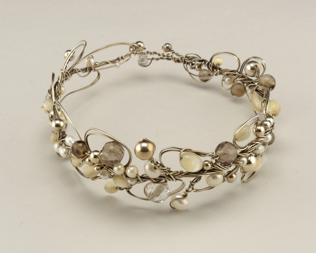 Threaded and hand-manipulated silver wire tiara with various semi-precious stones has a looped sculptural quality. This tiara also converts into a necklace.