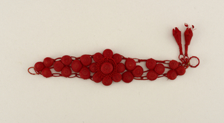 A red colored bracelet made of weaved balls, with a centered flower, dangling two teardrop shapes at the end. Part of a set.