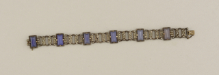 Bracelet of 6 alternating rectangular, half-cylindric, blue/grey moonstones with beveled ends, each prong-set in backless silver frame, each frame flanked by small rectangles punctuated with marquesites; attached to each rectangle are semi-circular and circular links connected by decorative, oblong, marquesite-set elements; clasp recesses into rectangular element at opposite end, small lock mechanism attached to side of clasp.