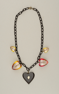 Necklace has charms in the form of hearts, one with bust of George VI.