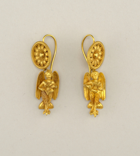 Each earring with circular ornament in open-daisy design from which hangs a fantastic figure (head and upper body, human with wings and feet of a bird).