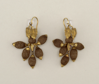 Earrings of five pendants and one ball made of brown hair arranged around a trumpet-shaped support of gold, placed below two gold leaves on a gold ring.