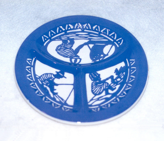 Thickly potted circular plate molded into three compartments by ridges.  Entire surface glazed white and then painted with royal blue.  Decoration consists of a rim of triangle-like forms surrounding three scenes of a young boy sailing, fishing, and playing with ducks (each in its own compartment).