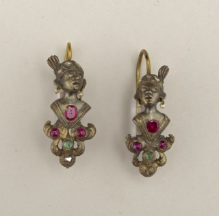 A and B: Gilt earrings in the form of a human head wearing a turban set with paste diamonds and pearl earrings; at the bottom, a lead ornament set with red and green stones.  Ring at the bottom suggests a part may be missing.