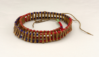 Made from bone segments strung together on leather with two rows of red and blue bead spacers; red, blue and green beaded tie ends.